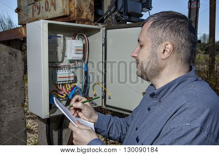Outdoor electric substation electrician engineer Writing Reading Of electricity Meter On Clipboard.