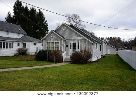 HARBOR SPRINGS, MICHIGAN / UNITED STATES - DECEMBER 24, 2015: A small gray home on Fourth Street in Harbor Springs.