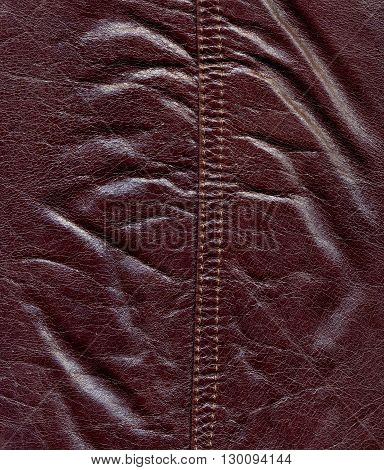 Texture of dark red natural leather, double seam