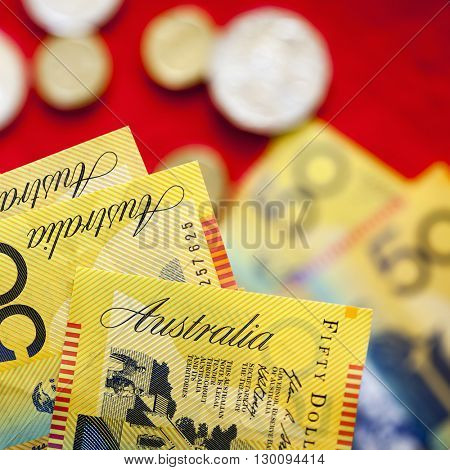 Australian fifty dollar notes over red background.  Blurred coins and notes behind.