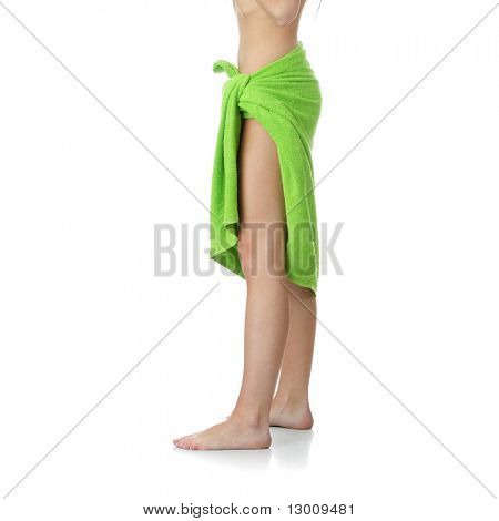 Nice shape of nude female body covered with green towel, against white background