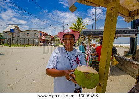 Muisne, Ecuador - March 16, 2016: Local street vendor posing happily with green coconut, beachside pacific ocean, beautiful blue sky.