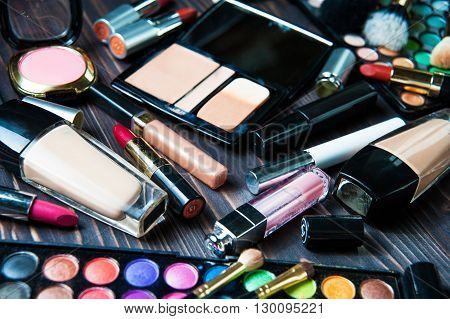 Various makeup products on dark wooden background