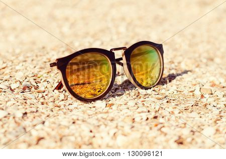 sunglasses in the sand at the beach. shallow depth of field