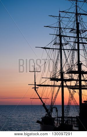 Passion to travel and thirst of adventures. Silhouette of the old ship at sunset.