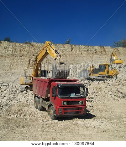 Excavator loads a truck with rubble in a quarry mining of stone