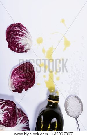 Radicchio red salad leaves with olive oil and salt. Top View, white background.