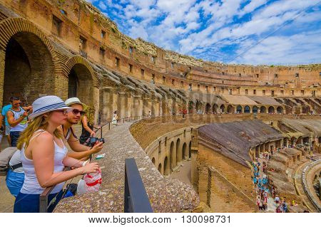 ROME, ITALY - JUNE 13, 2015: Turists looking a world heritage, Roman Coliseum. Great architecture.