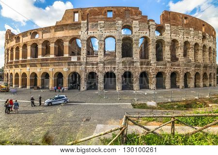 Rome, Italy - May 12, 2016: police cars, policemen and tourists in front of Colosseo, Colosseum, Flavian Amphitheatre, the largest amphitheater in the world and one of the symbols of Italy and Rome.