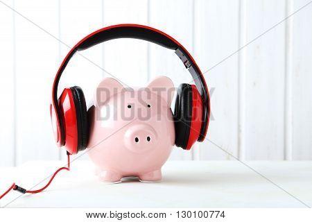Headphones On Piggybank On White Wooden Table