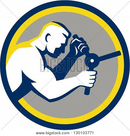 Illustration of a male worker opening safe handle viewed from side set inside circle done in retro style.