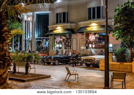 ADEJE, TENERIFE, SPAIN - DECEMBER 6, 2015: People at street cafe with tables in car look style at Adeje town on Tenerife island.