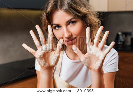 Portrait of a beautiful young lady  showing her hands dirty with flour