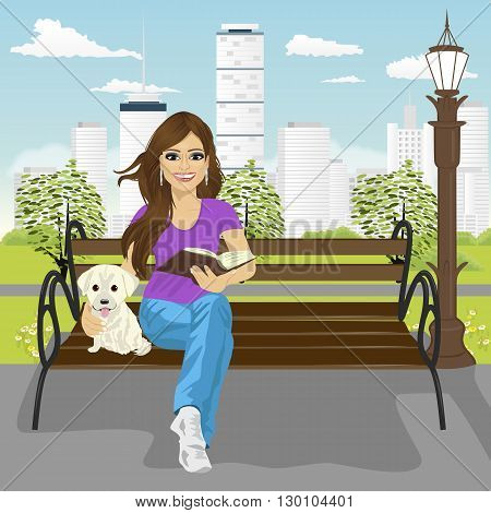 Young happy woman enjoying freetime in the city park in summer reading book sitting on a bench hugging labrador puppy
