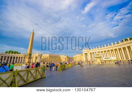 VATICAN, ITALY - JUNE 13, 2015: Outside Vatican Basilica, Saint Peter square with turists everywhere, stone path. Obelisk and fountaine,
