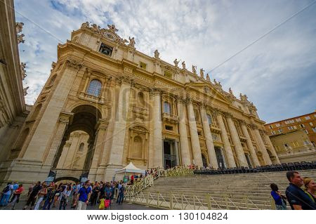 VATICAN, ITALY - JUNE 13, 2015: Saint Peter Basilica at Vatican in all its glory, summer day with summer light. Turists walking around