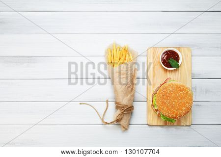 Burger and Chips. Hamburger and french fries wrapped in brown wrapping paper. Fast food take away at white shabby chic wood. Hamburger with tomato sauce. Top view, flat lay with copyspace