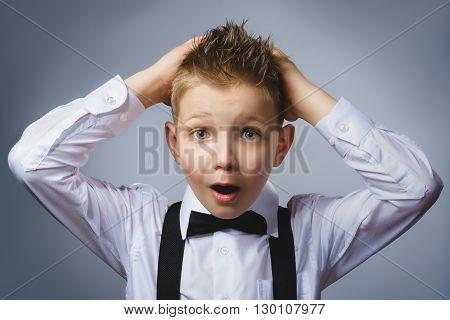 Closeup portrait headshot nervous anxious stressed afraid boy isolated grey background. Negative emotion facial expression.