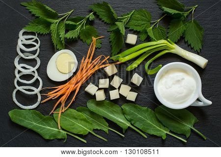 Ingredients for preparation Russian traditional vitamin soup of sorrel and nettles on slate surface. Flat lay