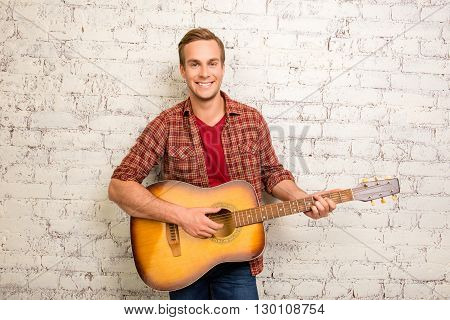 Cheerful Happy Man With Guitar On The Background Of Wall