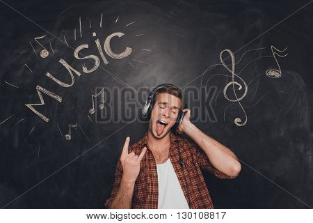 Cool Trendy Man In Headphones Listening Music And Showing Rock Gesture