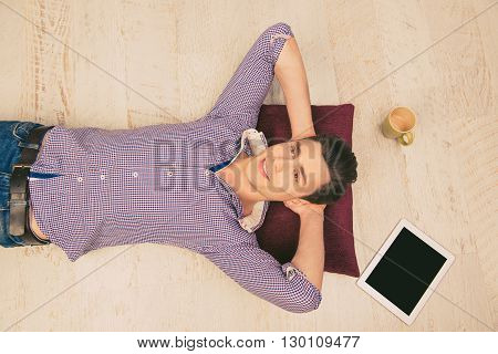 Close Up Top View Photo Of Smiling Man Lying On The Floor With Cup And Tablet