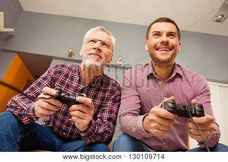 Two Cheerful Happy Men Playing Video Games With Joysticks