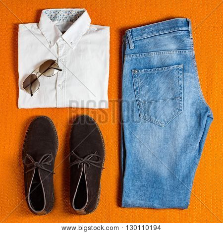 flat lay men's clothing on orange background
