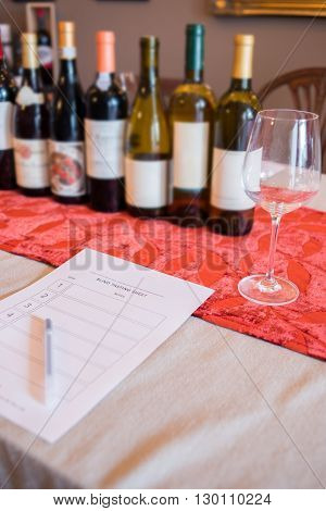 A row of wine bottles and an empty wineglass by a blank blind tasting form and pen on a restaurant table.