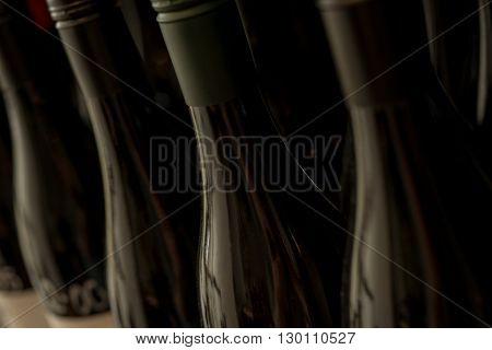 A row of unopened dark bottles of wine or liquor