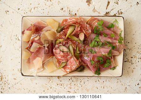 Assorted deli meat or cold cuts and greens in a rectangular plate.