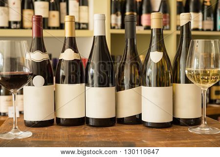 A row of bottles of wine with blank labels between wineglasses on wooden surface and a wine collection in the background