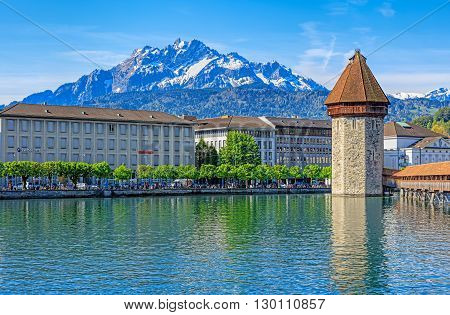 Lucerne, Switzerland - 7 May, 2016: view on the Reuss river with the Water Tower and the Chapel Bridge Mt. Pilatus in the background. Lucerne is a city in central Switzerland it is the capital of the Swiss Canton of Lucerne.