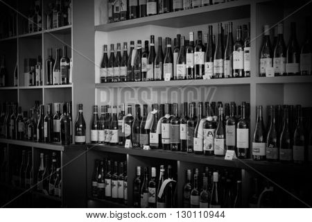 Monochrome image of bottles of wine on shelves of a storehouse