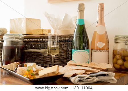 Two bottles of unopened, blank-labeled champagne along with a serving of cheese and crackers