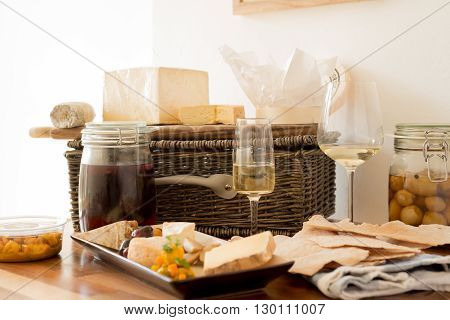 Two glasses of wine with servings of cheese and biscuits alongside a jar of honer, olives, and a wicker basket.