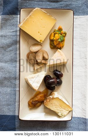 Slices of gourmet cheese with vegetable mush side dish, cooked shallots, and fruits in a rectangular platter