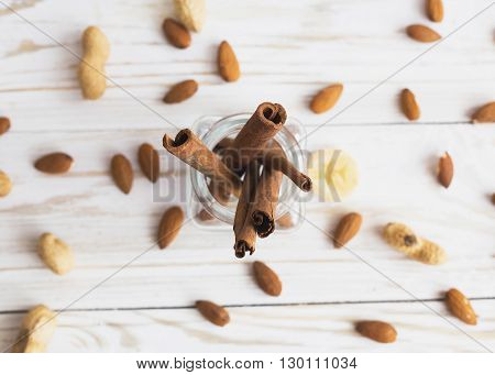 Aroma spices. Cinnamon peanuts and almonds on the vintage wooden table