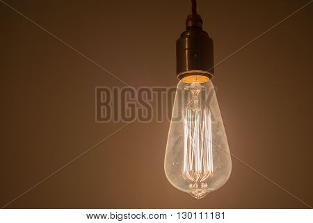 A lit up incandescent light bulb with multiple filaments