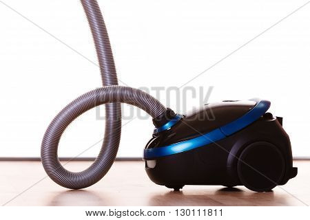 Vacuuming the house. Vacuum cleaner on wooden floor. Housework