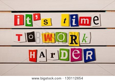 It's time to work harder motivational quote written with color magazine letter clippings on wooden board. Concept  image.