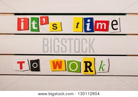 It's time to work - written with color magazine letter clippings on wooden board. Concept  image.