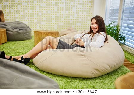 Business woman relaxing during her lunch break on a puff in the break lounge