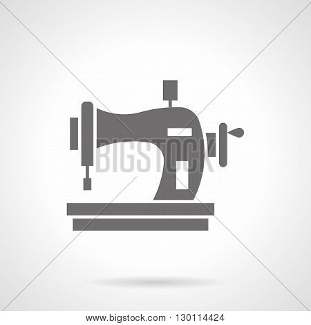 Manual sewing machine with thread spool. Tailor equipment, homemade crafts and hobbies to sewing fashionable clothes. Symbolic black glyph style vector icon.