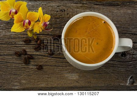 Coffee mug and yellow orchid on the wooden background. Coffee cup. Cup of coffee. Strong coffee. Coffee break. Coffee mug. Strong coffee. Morning coffee.