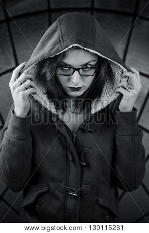 Sinister black and white portrait. Girl in the hood with gaze over her glasses and skull tattoo on the finger. On abstract dark stained-glass background