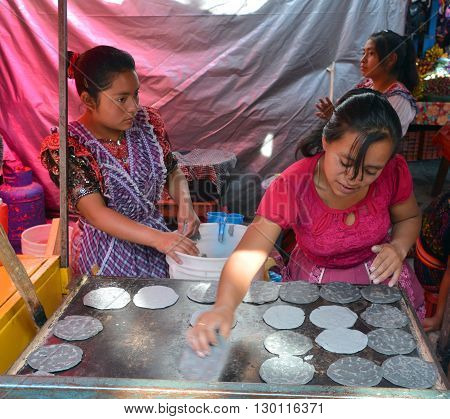CHICHICASTENANGO GUSTEMALA APRIL 29 2016: Woman cooking tortillas in the Chichicastenango Market. This native market is the most colorful in Central America