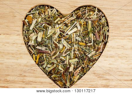 Dried herb leaves heart shaped on wooden surface. Herbaceous dry aromatic plant. Healthy cooking concept.