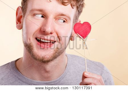 Freedom of feelings. Young happy smiling man with little red heart on stick. Romantic man dreaming of his love relationship.