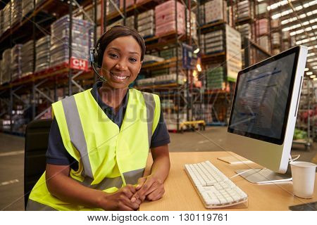 Woman with headset in a warehouse office looks to camera